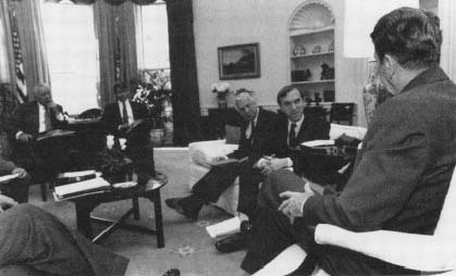 National Security briefing in the Oval Office with Oliver North at rear. (Courtesy, Ronald Reagan Library)