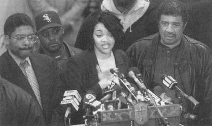 Tawana Brawley with Alton Maddox (left) speaks to supporters before the defamation lawsuit against the men who had advised her. (AP/Wide World Photos)